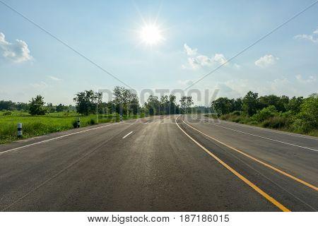 asphalt road and sun on blue sky