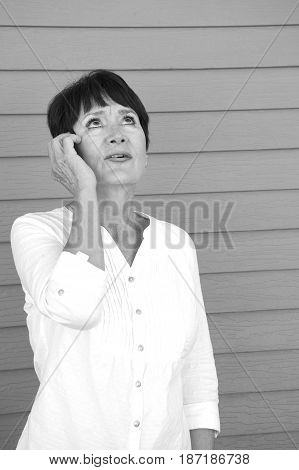Mature female beauty talking on her cellphone outside.