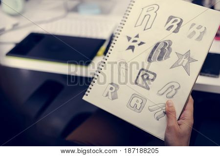 Hand Holding Notebook With Drew Brand Logo Creative Design Ideas