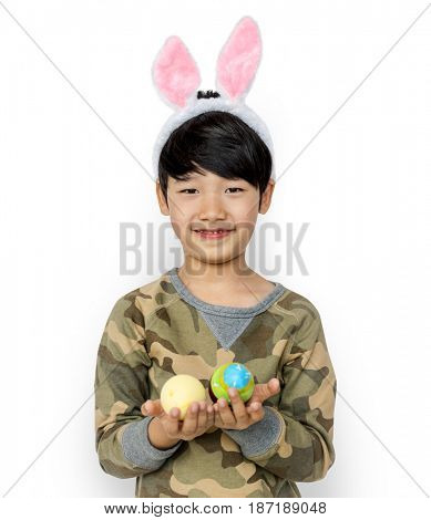 Kid with a bunny hairband holding eggs