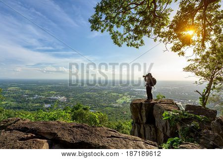 Photographer is taking a picture of view of natural scenery on rock.