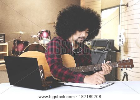 Afro man composing a song and writing on clipboard while listening music on earphone in music studio