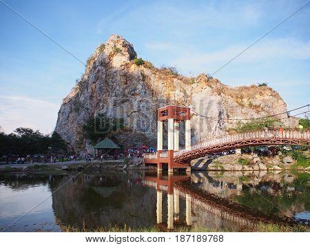 Mountain and long vintage bridge across lake with reflection at Khao Ngoo Rock Park or Thueak Khao Ngu Ratchaburi Province Thailand.
