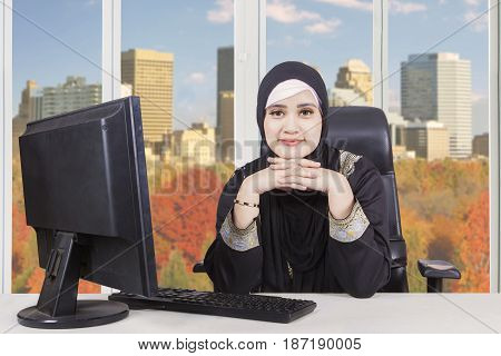 Arabian businesswoman daydreaming in the office while looking at the camera and working with laptop computer