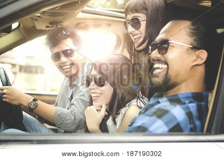 Picture of a young Asian man driving a car while travelling with his friends