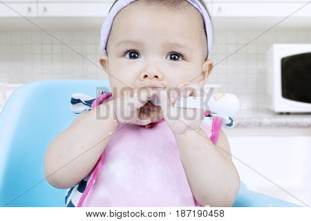Portrait of a cute baby learns to eat porridge and bites the spoon with dirty hands in the kitchen