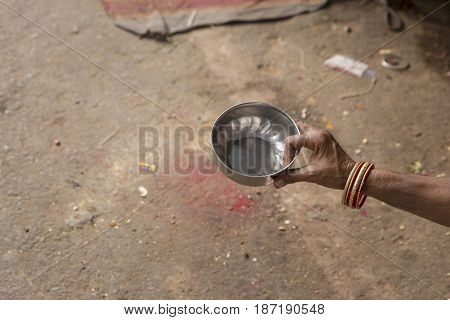 small water dipper for begging in hand of indian beggar