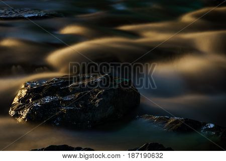 Long exposure shot of fast running water from river flowing over rocks at night