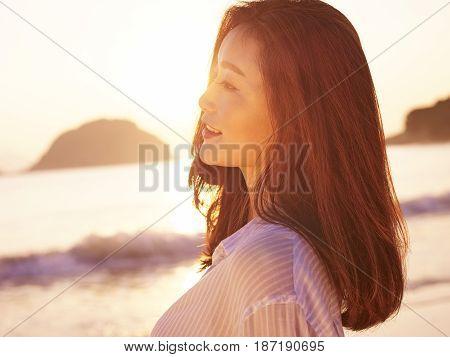 young asian woman enjoying the early morning sunlight on beach.