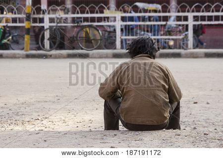 dirty homeless sit on sidewalk in chandni chowk of Old delhi India. selective focus on foreground.