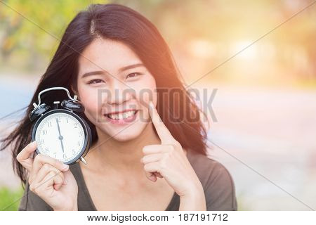 Thai Asian Women Show And Point Her Face Aside With Clock, Time Reverse Back To Baby Skin Concept.