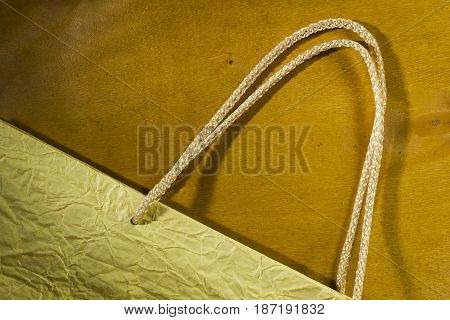 Rope handles from a paper bag on a wooden background