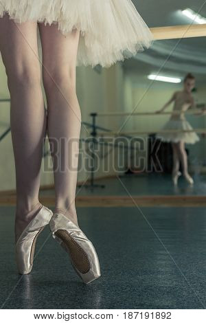 Ballerina in pointe shoes and tutu standing on toes at the bench. Reflection in the mirror in the ballet class. Classical ballet. Prima ballerina. Shooting close-up.