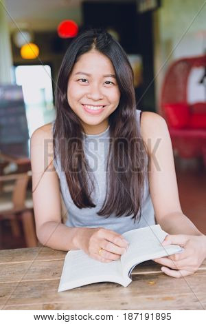 Enjoy relax times with reading book Asian women Thai teen smile with book in coffee shop