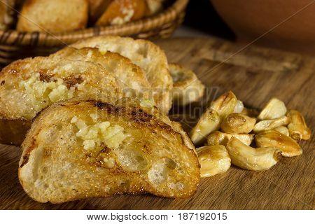 Fried garlic bread and garlic closeup on a wooden board