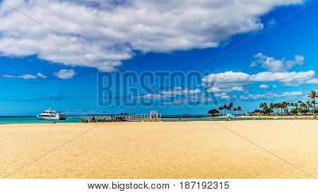 The beautiful sand of Waikiki beach under blue and partly cloudy sky makes it one of the world's most famous beaches. Located in Honolulu on the Hawaiian island of Oahu