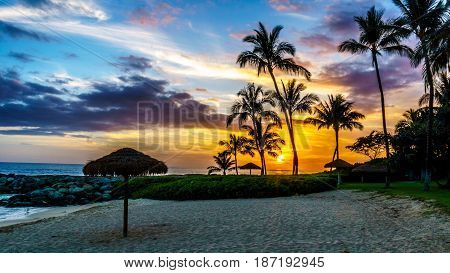 Sunset over the Lagoon and beach with Palm trees and colorful sky at the resort community of Ko Olina on the West Coast of the Hawaiian island of Oahu