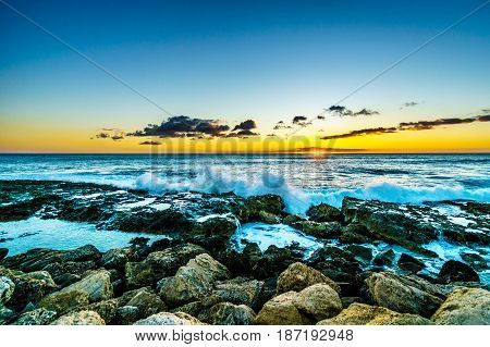 Sunset over the horizon with a few clouds and waves crashing on the rocky shores of the west coast of the tropical Hawaiian island of Oahu