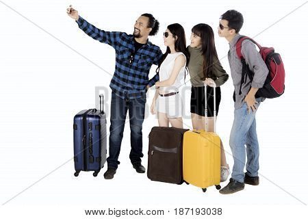Multi ethnic group of friends taking selfie picture with smartphone while standing together isolated on white background