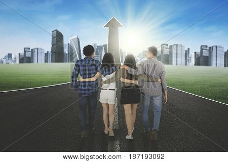Back view of group of friends walking on road turning into an upward arrow while embracing to each other