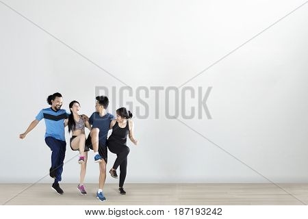 Group of cheerful multiracial people doing workout together while jumping and embracing to each other