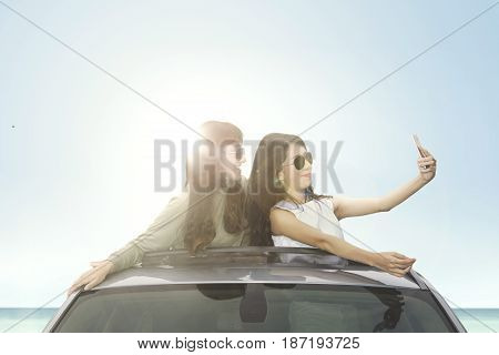 Two happy women taking selfie photo with smartphone on a car sunroof on the beach