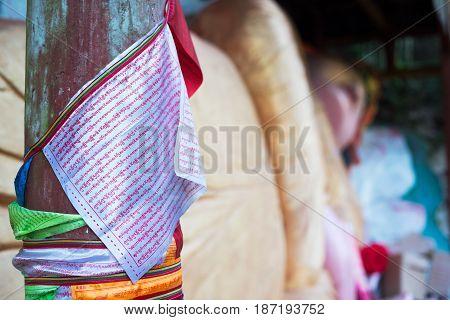 Hongya Sichuan Province China - Apr 29 2017: Tibetan script on flags hanging near a lying buddha in Gaomiao temple