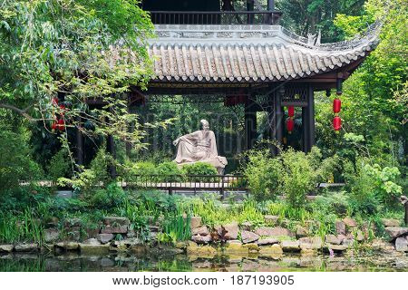 Meishan Sichuan Province China - Apr 30 2017: Su Shi poet sculpture behind a pavilion in Meishan
