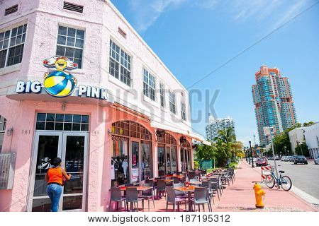 Miami, USA- June 28, 2016; Women approaches door of Big Pink retro era restaurant on Collins Avenue with empty table outside on pavement.