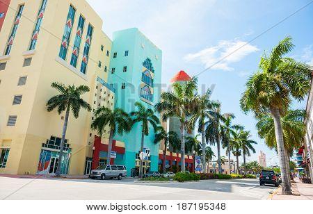 Miami, USA- June 28, 2016; Typical Miami retro styled buildings across Washington Avenue on shady side of street.