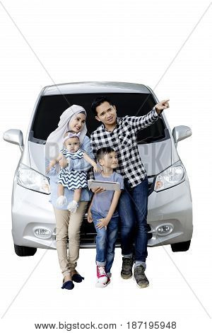 Muslim family using a digital tablet and sitting on the hood of their car while looking at something