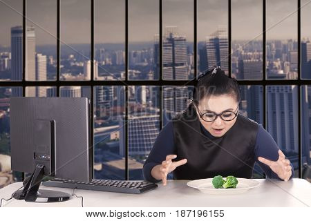 Portrait of overweight female worker looks hungry and want to eat broccoli on a plate shot in the office