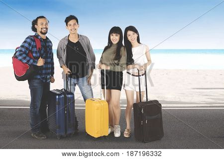 Multi ethnic of young people standing on the road while holding suitcase on the beach