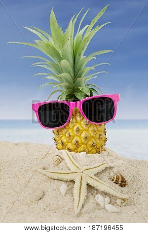 Pineapple fruit with a sun glasses starfish and seashells on the sand at tropical beach