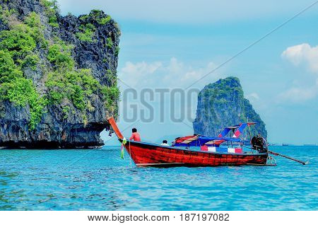 A small marine tour boat sailing in the Andaman Sea full of islands.