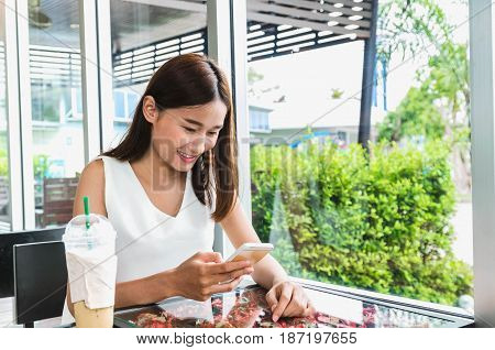 Women use the phone in a coffee shop for shopping on line