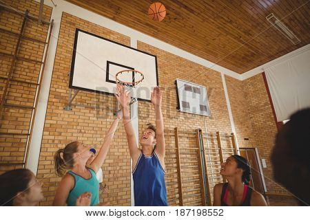 Excited high school kids scoring a goal while playing basketball in the court