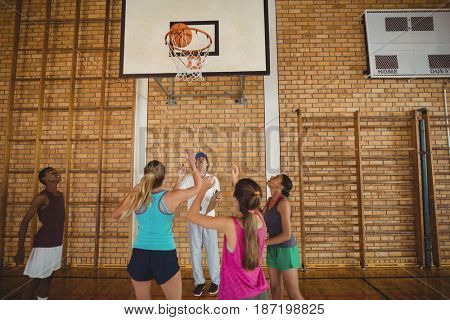 Coach helping high school team to score a goal while playing basketball in the court