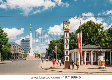 Riga, Latvia - July 2, 2016: People Walking Near Local Landmark Is Laima Clock In Sunny Summer Day. Now It Is One Of Landmarks And An Advert For The Laima Chocolate Company