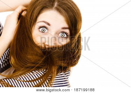 Haircare and hairstyling concept. Woman having face covered with her dark brown hair.