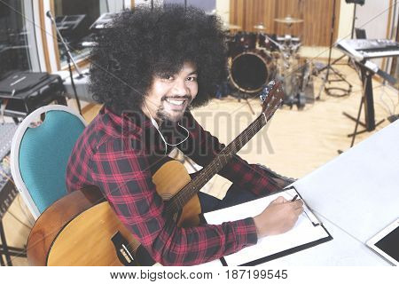 Young man composing a song and writing on clipboard while smiling at the camera in the music studio