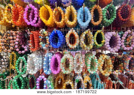 Wide range of colorful fashionable gemstone bracelets and bead jewelry in souvenir shop at the Chinatown district. The Chinatown is a popular tourist attraction of Asia.