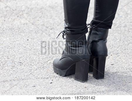 Legs of a girl in black heels .