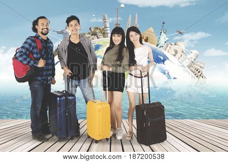 Multi ethnic of young people standing on seaside while holding suitcase with famous landmark background