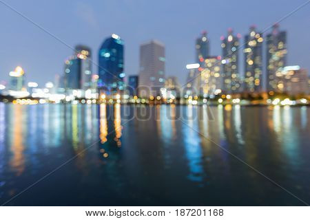 Twilight blurred bokeh light Office building with water reflection abstract background