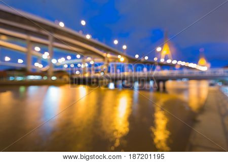 Twilight blurred light suspension bridge and highway intersection river front abstract background