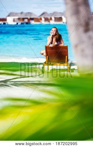 Beautiful woman on the beach, attractive girl wearing sexy swimsuit tanning on the sunbed, enjoying summer vacation on the luxury beach resort, Maldive islands