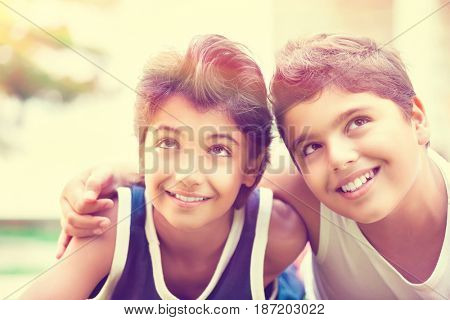 Portrait of a two happy boys lying down on the field in sunny day, best friends spending time together, summer holidays in the camp