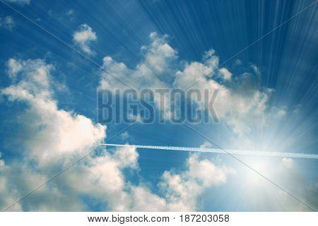 Rays of bright sun on a blue summer cloudy sky