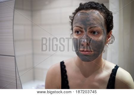 Woman with hygiene clay mask applied on face.